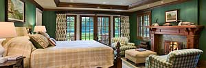 luxury master bedroom of restored historic Montana cabin towards windows and views of Swan Lake