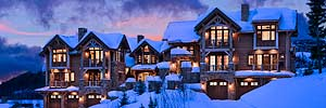 exterior elevation at twilight of luxury rustic condominiums at The Yellowstone Club mountain resort